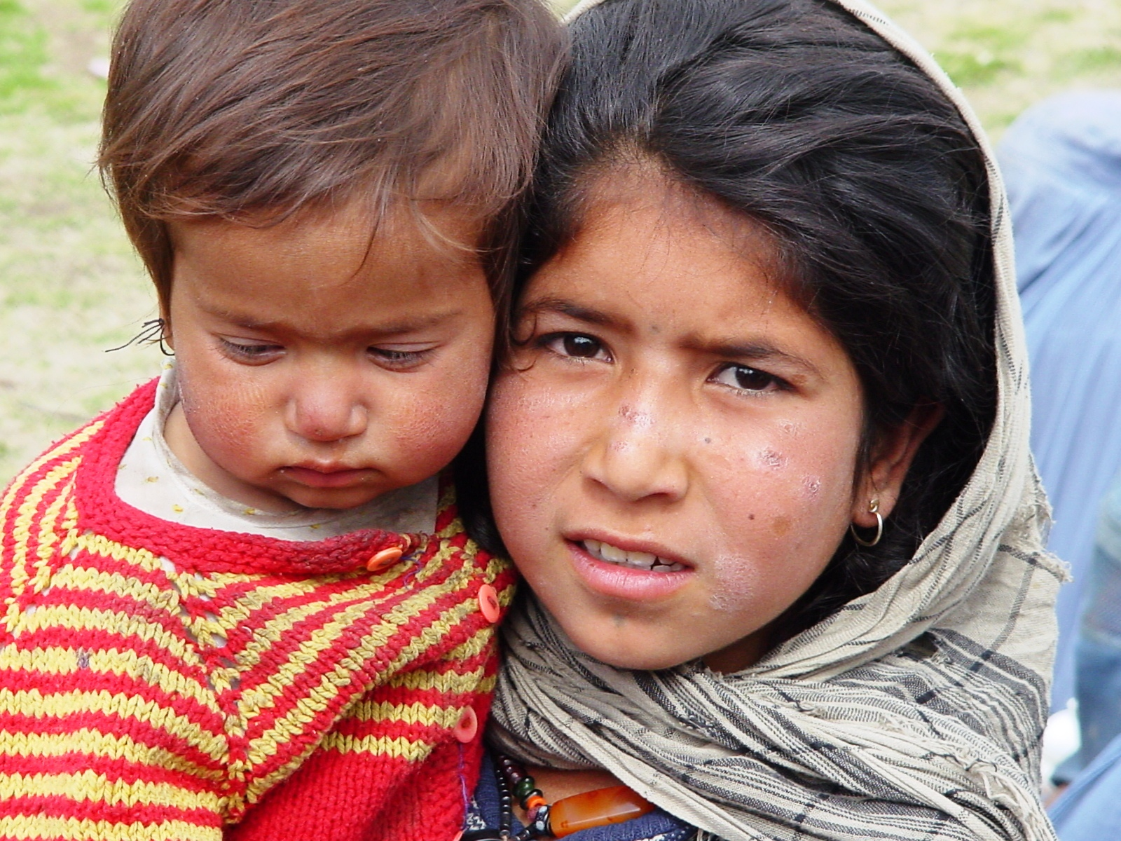 A little girl holding her baby brother with dirt on their faces.