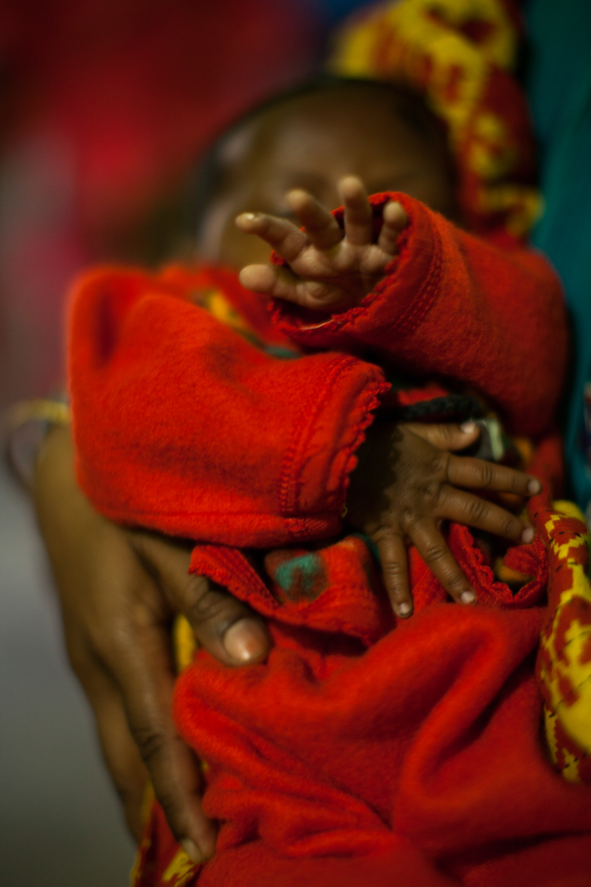 A baby's hands covering her face to comply with our child protection policy.