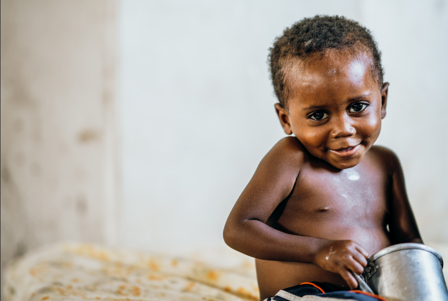 A little malnourished boy smiling holding his cup of therapeutic milk.
