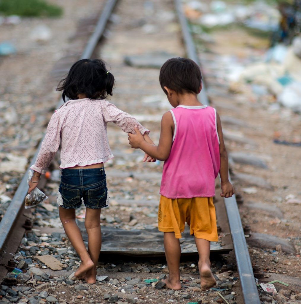 Saving Moses - Who Are We Again? - One little boy and one little girl holding hands walking down abandoned railroad tracks.