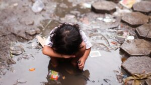 Surviving the Underpass - a little girl in Cambodia standing in a mud puddle.
