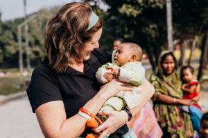 Hanging by a Thread: The Saving Moses Journey - Saving Moses Book - Founder Sarah holding a baby in Bangladesh
