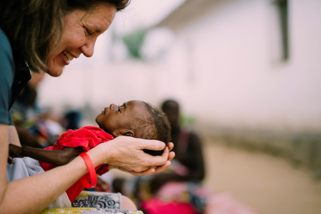 Severe Acute Malnutrition - More Than Being Hungry - Founder Sarah Bowling holding a malnourished baby at our malnutrition clinic.