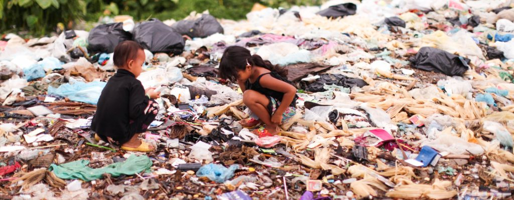 Work with Children, End Poverty - two children playing in trash.