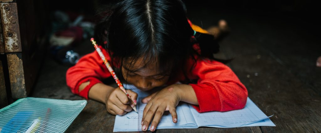 Work with Children, End Poverty - a little girl doing her school work.