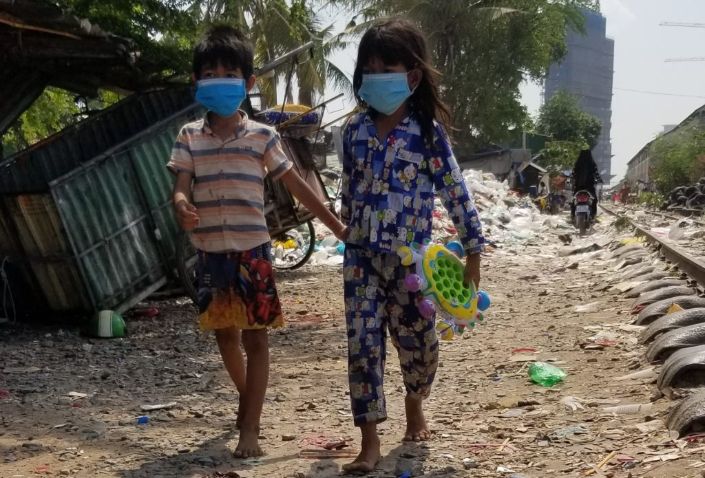 Why Should I Care About Babies Across the World? - Two children wearing masks and walking through trash near the railroad tracks.