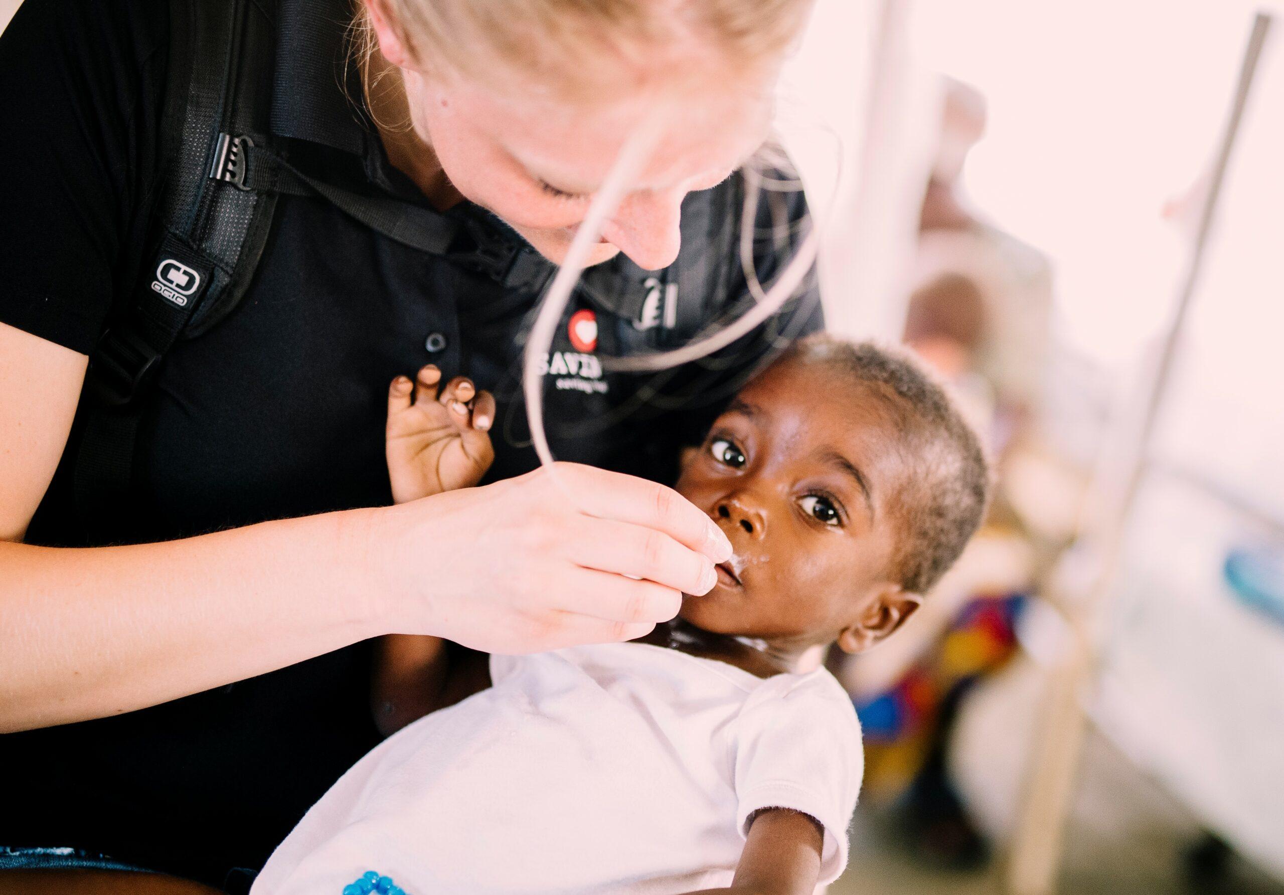 Humanitarian Aid - Executive Director, Heidi, feeding a baby in Angola.