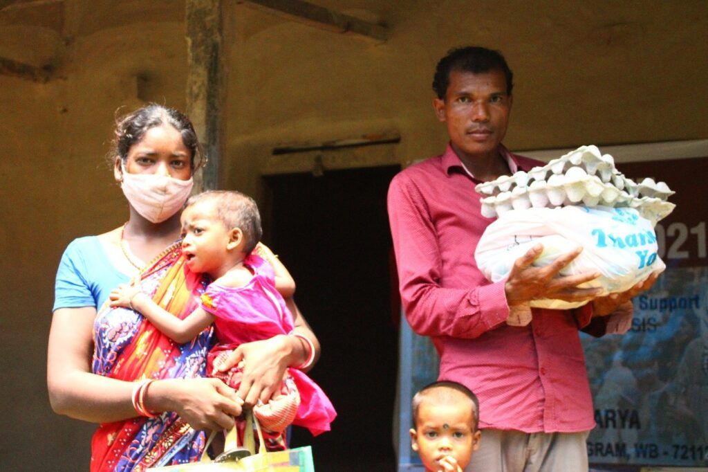 Parents with their baby and toddler receive a care box from a local Intensive Care Unit during the second wave of the COVID-19 pandemic in India, 2020