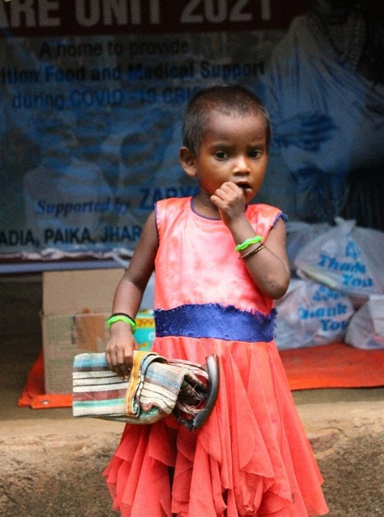 A toddler girl in front of relief supplies being distributed at a local Intensive Care Unit in rural India during the second wave of the COVID-19 pandemic