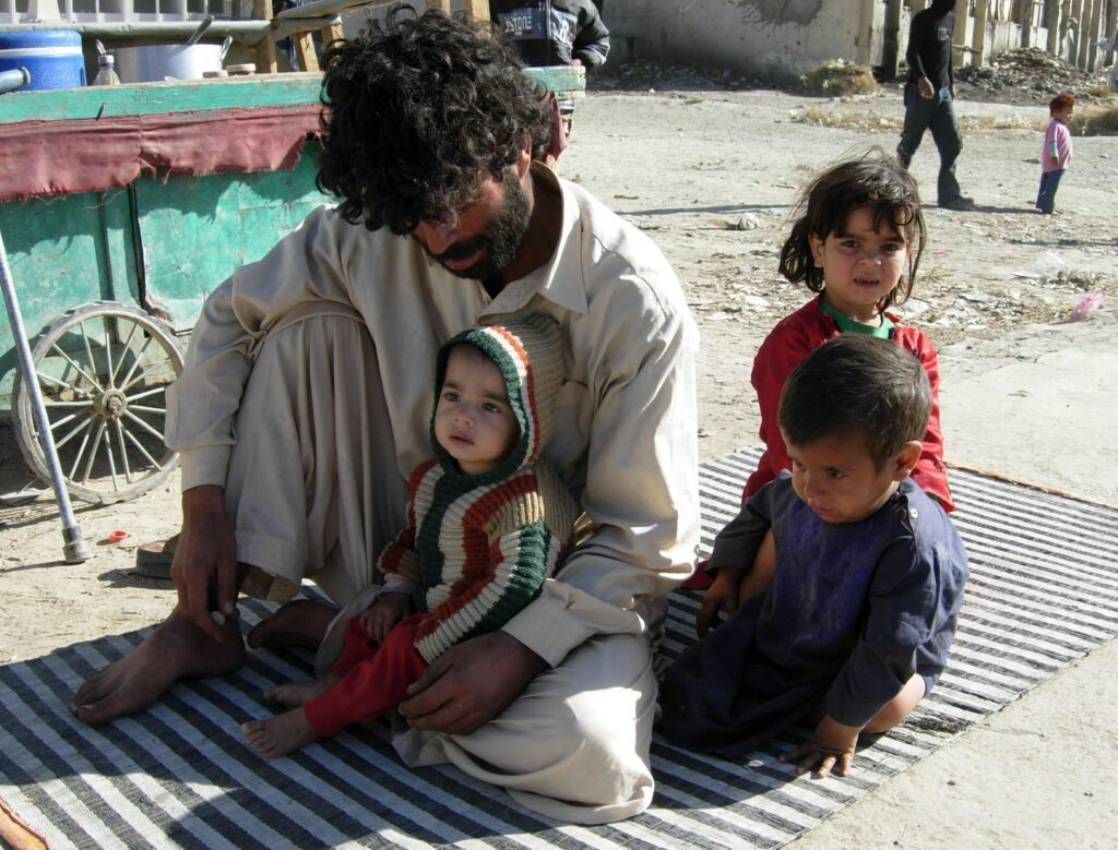 an Afghan man with his children outside
