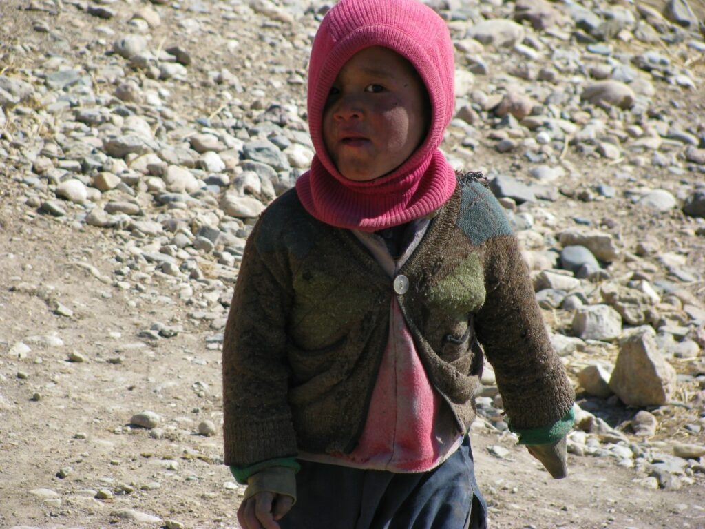 An afghan child in a sweater outside
