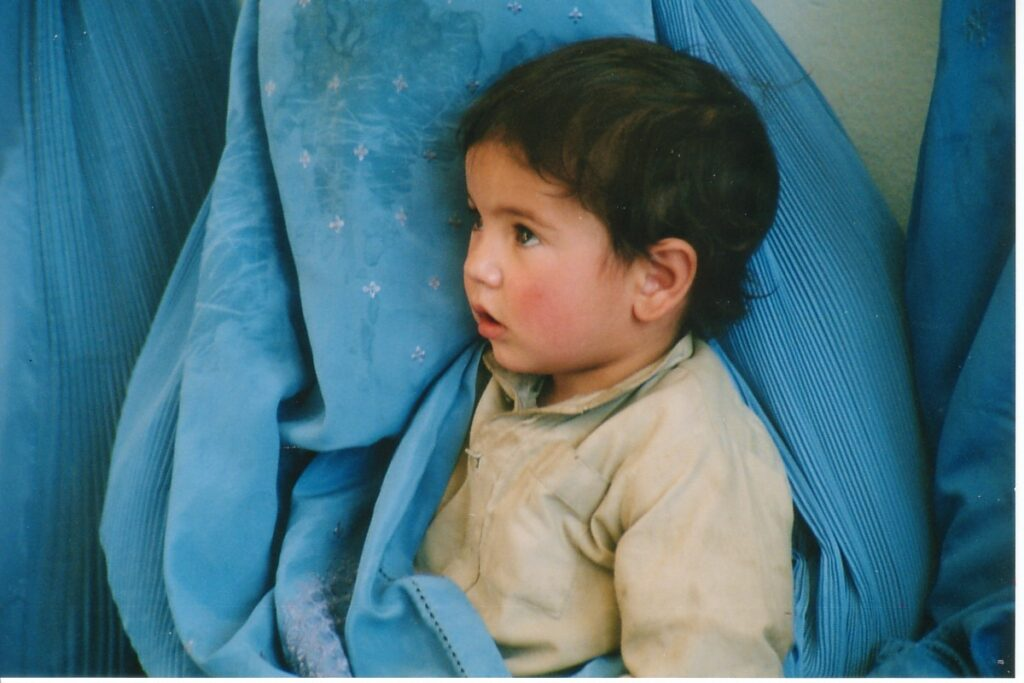 an afghan child in their mothers arms, covered by veil